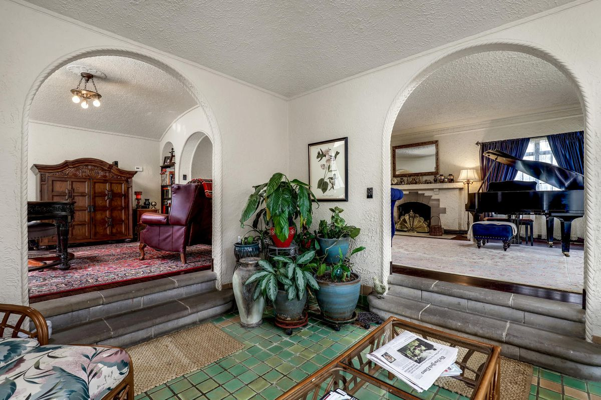 A smaller room with glazed green tiles leads to two separate rooms through arches and two small steps.