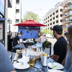 Chicago Blackhawk fans Nate Campbell, left, Eric Baumgartner, center, and Jessica LaPorte, right, enjoy drinks and food at WestEnd near Madison St and Ada St during the Blackhawks game against the Edmonton Oilers, Friday, Aug. 7, 2020. | Tyler LaRiviere/Sun-Times