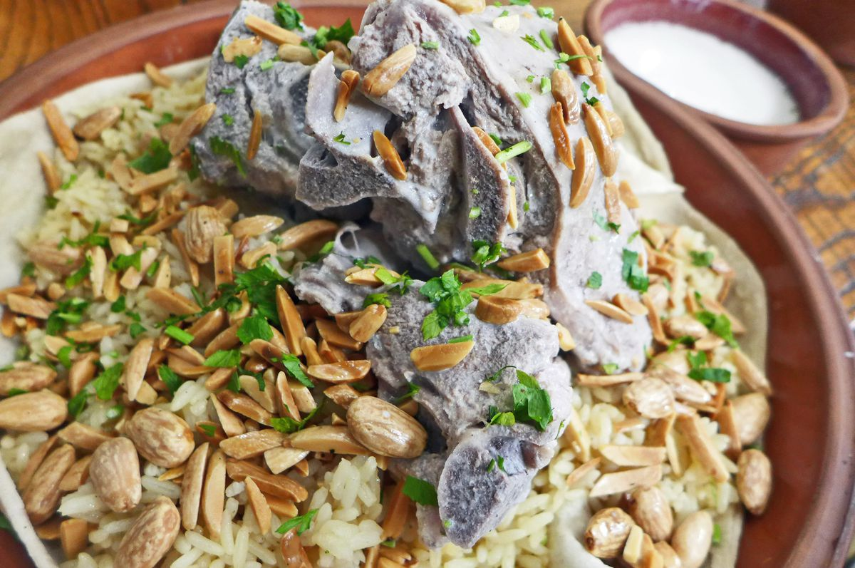 A bony hunk of meat in the middle on top of rice with bread underneath, and almonds scattered over all.