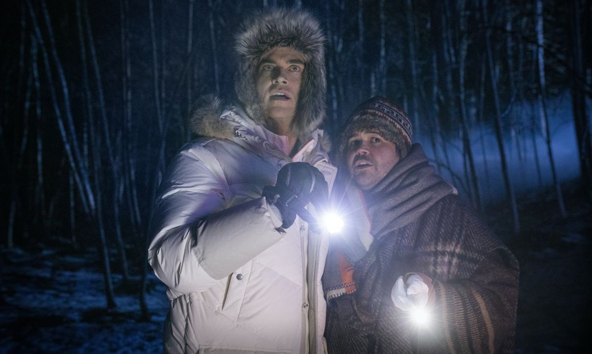 Cheyenne Jackson and Harvey Guillén huddle together outdoors, clutching flashlights, in Werewolves Within