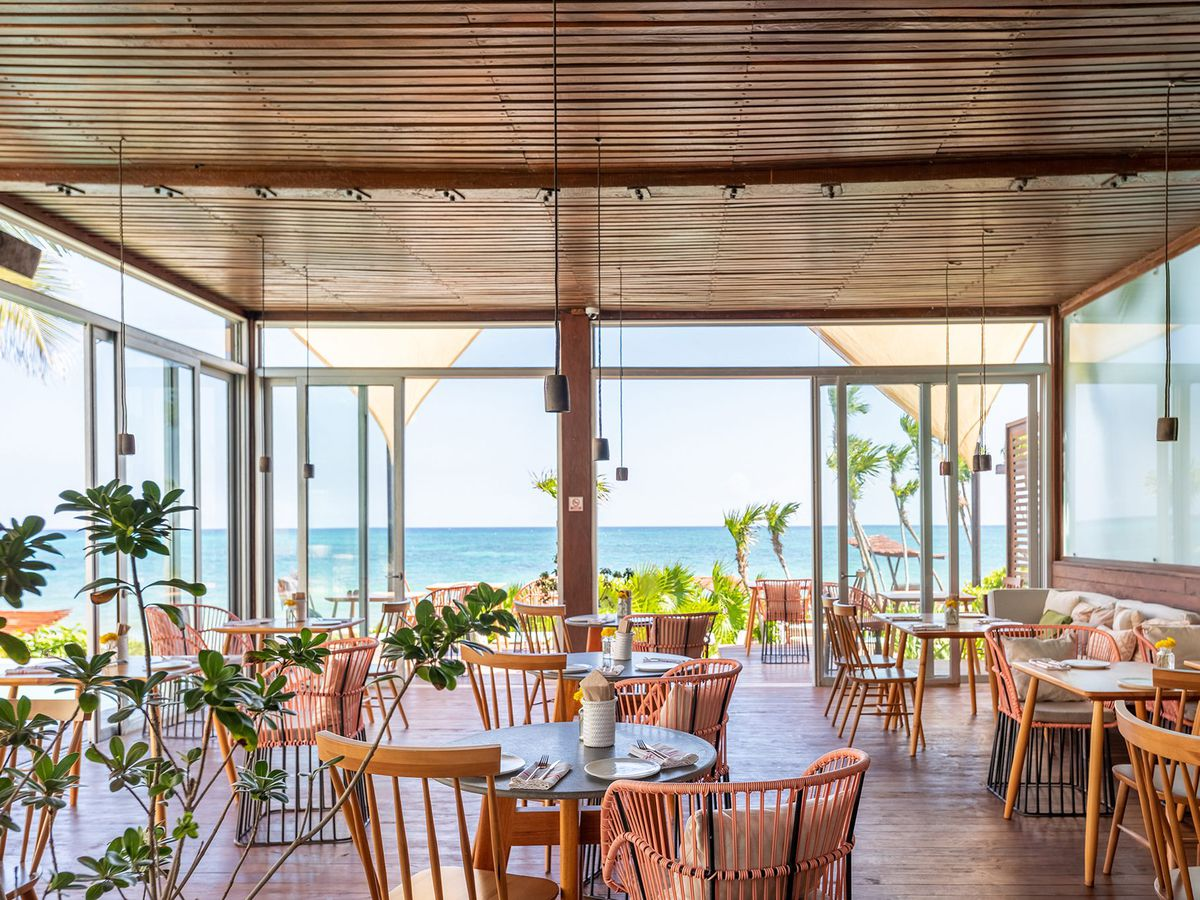 An open-air dining room looking out on the sea with empty tables set for breakfast