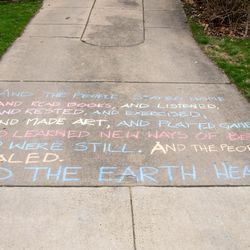 """A paraphrased version of Kitty O'Meara's """"And The People Stayed Home"""" poem is written in chalk on the driveway of a home in Riverside."""