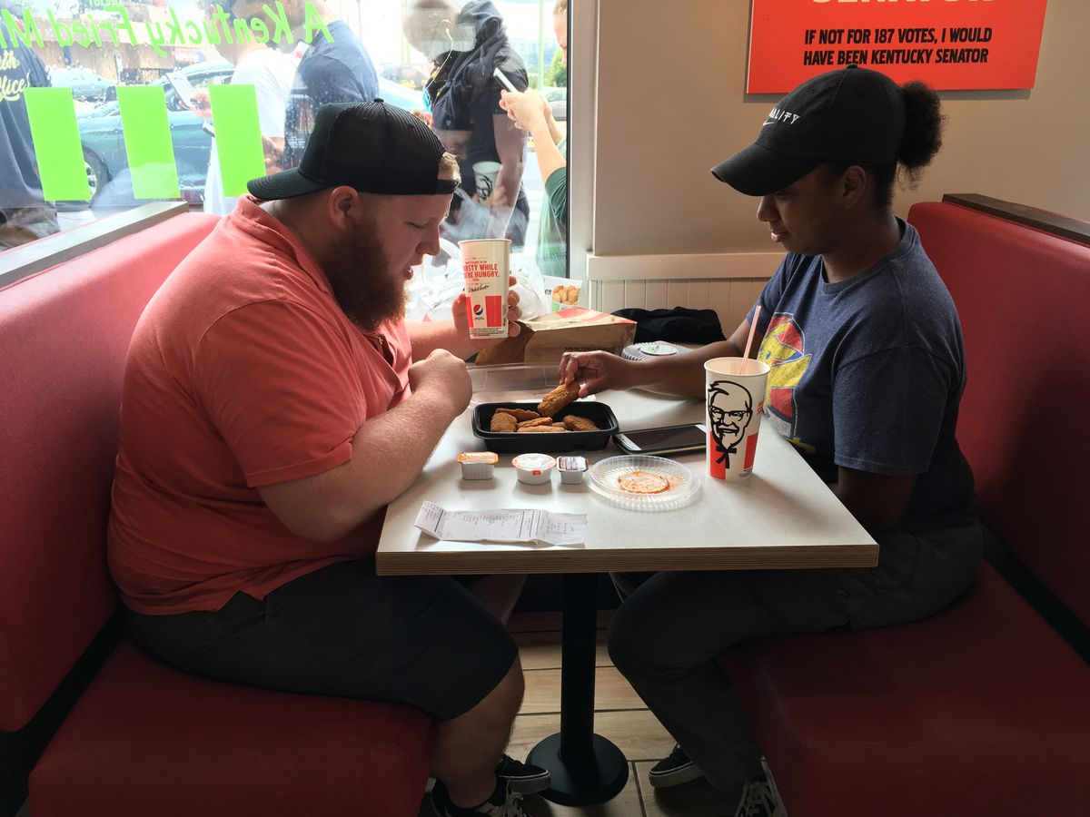 A couple eating vegan chicken nuggets and wings at a KFC booth