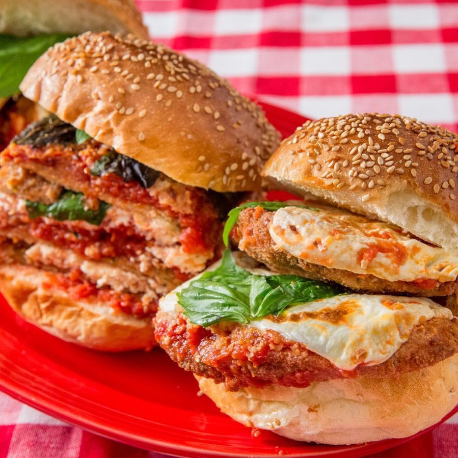 Two sandwiches, one filled with eggplant and the other chicken Parmesan