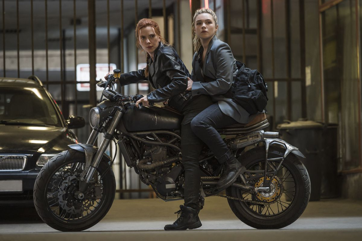 Scarlett Johansson and Florence Pugh, wearing black and perched on a motorcycle together, in Black Widow