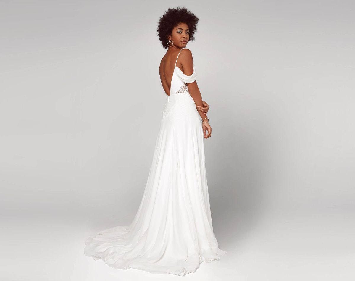 78f5b3b19 ... A model wearing a white wedding gown with an open back, thin straps, and