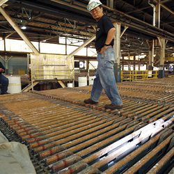"""Kennecott's Daniel Kim walks on tanks of cathodes and anodes in the tank house as Kennecott shows off the copper production process, including a behind-the-scenes looks at the operations of the refinery, tank house, stripping area, bundling and loading during its """"Heavy Metal Tour"""" on Wednesday. The copper they're showing off will be sent elsewhere for fabrication and then come back to Utah to be used in the Utah Museum of Natural History's new building, the Rio Tinto Center."""