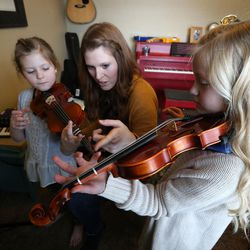 Ruby, 7, and Penny, 8, practice violin with their mother Emily Widdison at home in Saratoga Springs, Utah, Friday, Jan. 8, 2016.