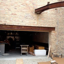 Rusted steel beams hang over the brick-walled back patio