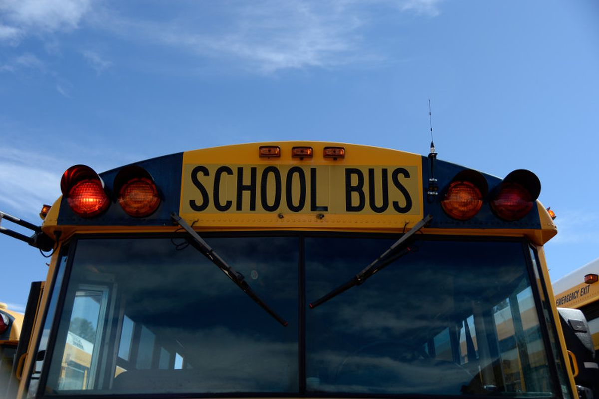 Looking head-on at the front of a yellow school bus.