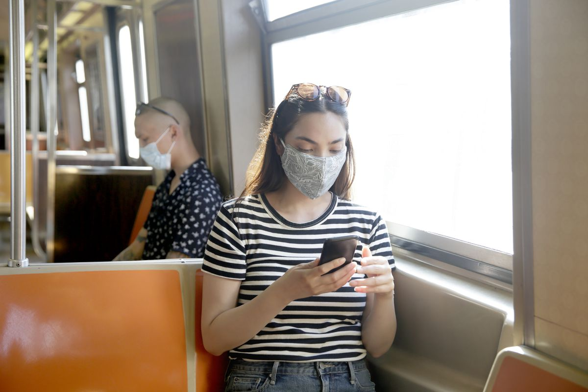 Two face-masked people sitting in a subway car, each looking at their phone.