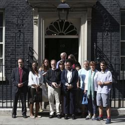 """Victims, volunteers and community leaders from the Grenfell Tower fire pause on the steps outside 10 Downing Street following a meeting with British Prime Minister Theresa May, after a fire engulfed the 24-storey building, in London, Saturday June 17, 2017. The meeting comes a day after May was heckled during a visit to the west London neighborhood where Wednesday""""™s inferno took place. At least 30 people have been killed, hundreds of others have been left homeless and dozens of others are missing."""
