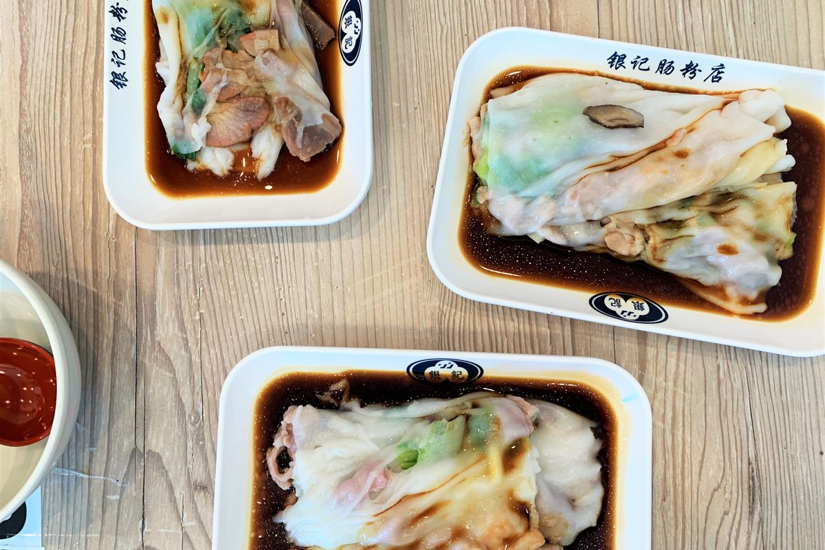 Three plates of Chinese rice rolls filled with meat and shrimp and covered with light soy sauce on a wooden table.