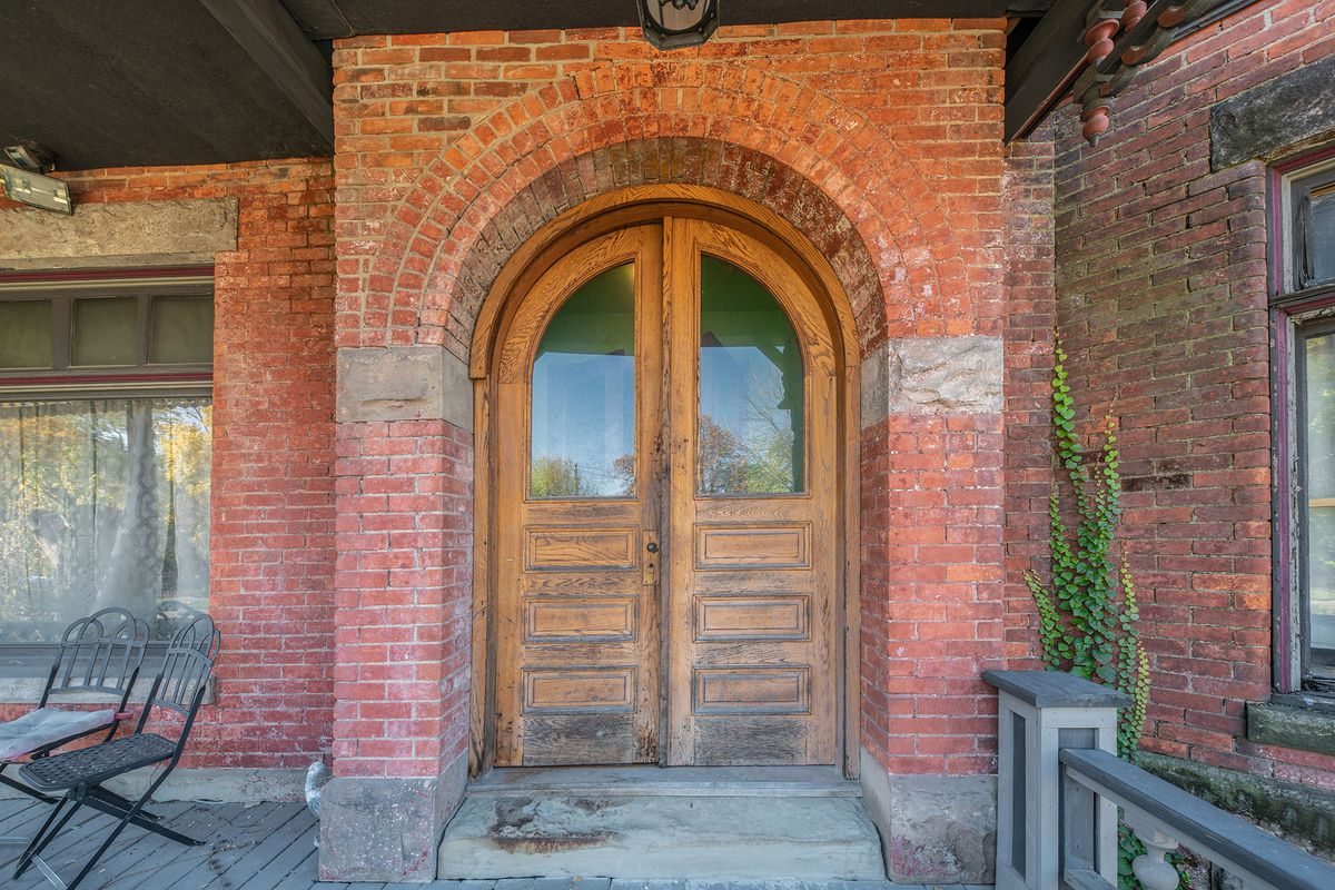 Large arched front entrance with double wood doors.