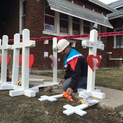 Greg Zanis of Aurora, mounts crosses on the front lawn of a Gage Park home, one for each of the six people found dead inside the house in 2016.