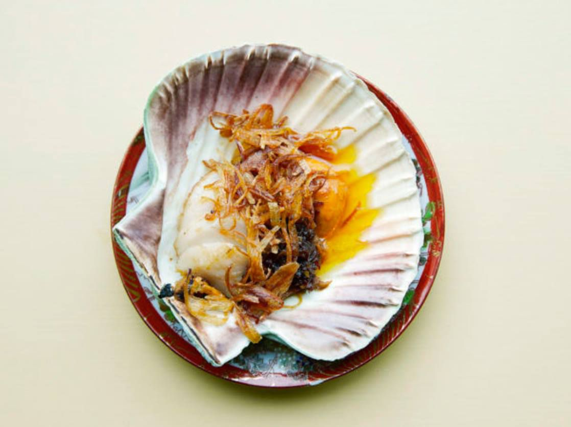 As seen from above, a scallop served in its shell topped with fried shallots and a light brown XO sauce