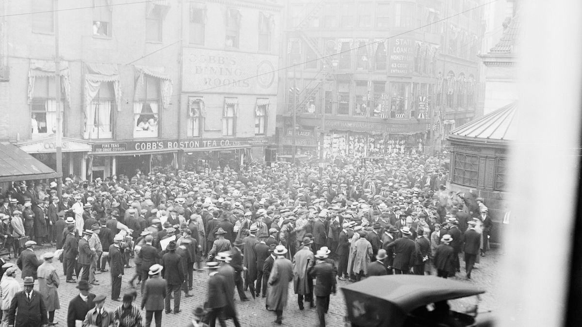 An old photograph of an immense crowd converging on a city street corner.