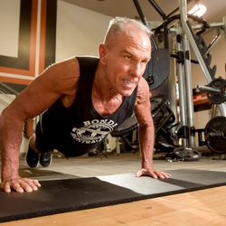 George Hood, 62, performs some push-up in the fitness room at his apartment complex on Wednesday, Feb. 26, 2020 in Naperville, Ill. Hood recently broke the Guinness World Record time for planking with a time of 8:15:15.