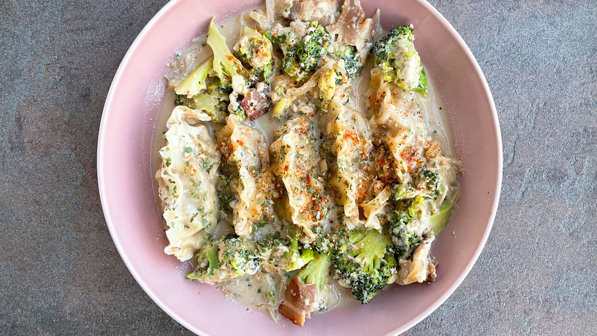 Frozen dumplings cooked in milk served in a dish with chopped broccoli and bacon.