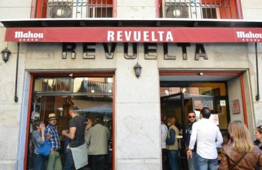 The stone exterior and patio awning of Casa Revuelta, with customers spilling out of the open doorways into the street.
