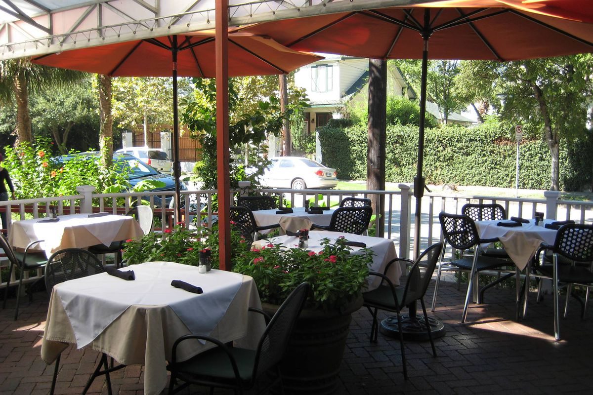 exterior shot of a shady, umbrella-lined patio where the tables are covered in white cloths