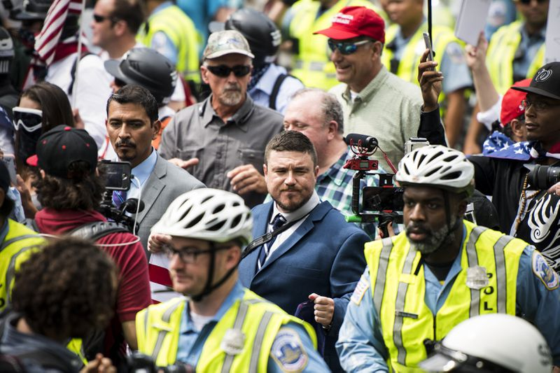 Jason Kessler, center, organizer of the Unite the Right protest, marches with a couple dozen white nationalists under police escort to their rally in Lafayette Square park.