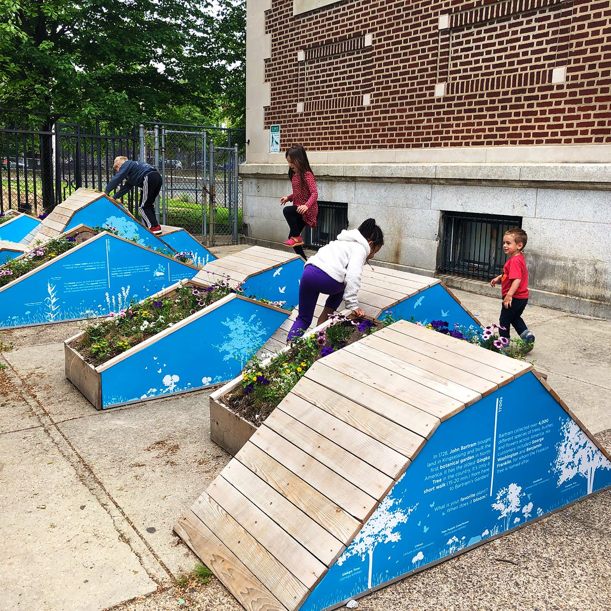 Children play on structures built of wooden planks with sections containing dirt for plants to grow.