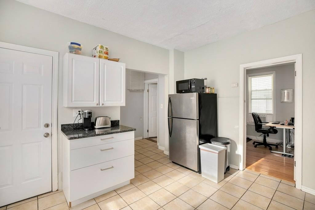 A corner of a spacious kitchen with a narrow counter and fridge in the corner.