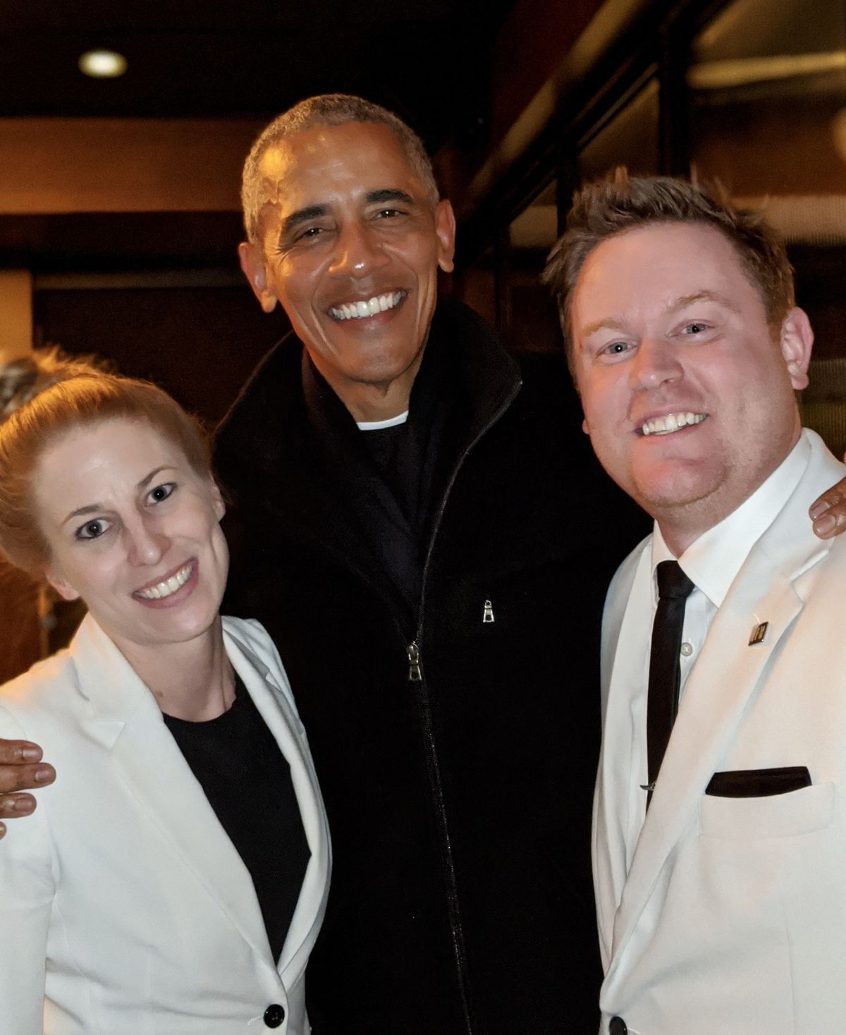 President Barack Obama poses with two employees in white jackets.