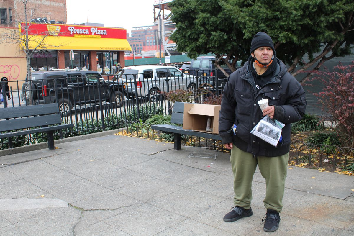 Angel Melendez stands in front of the bench where a friend, Flaco, was found dead of a suspected overdose.