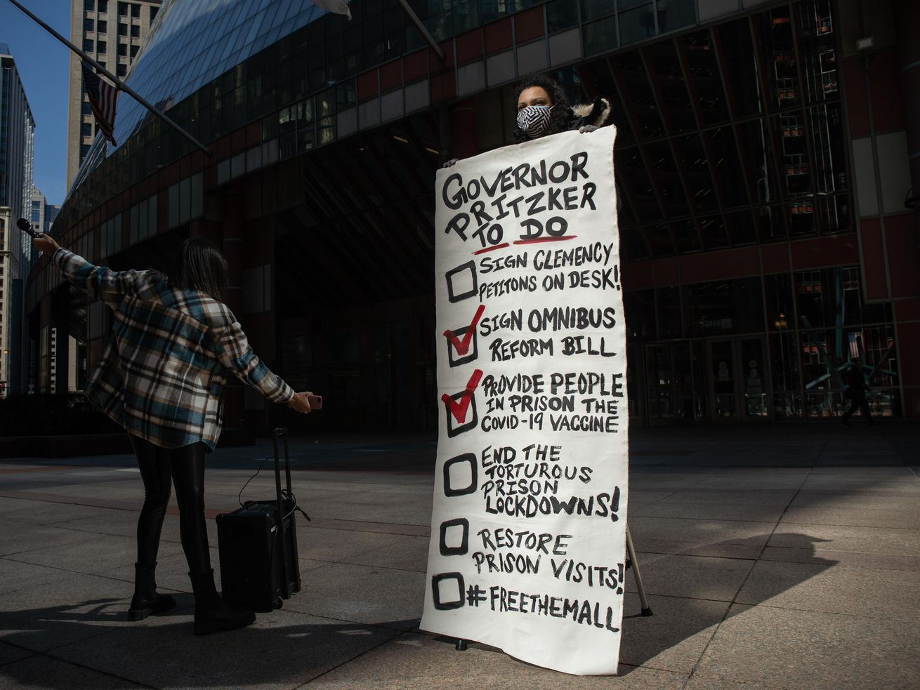 Zana Marino, an End Illinois Prison Lockdown Coalition member, holds a list of demands for Gov. J.B. Pritzker outside the James R. Thompson Center in the Loop, Friday morning, March 9, 2021.