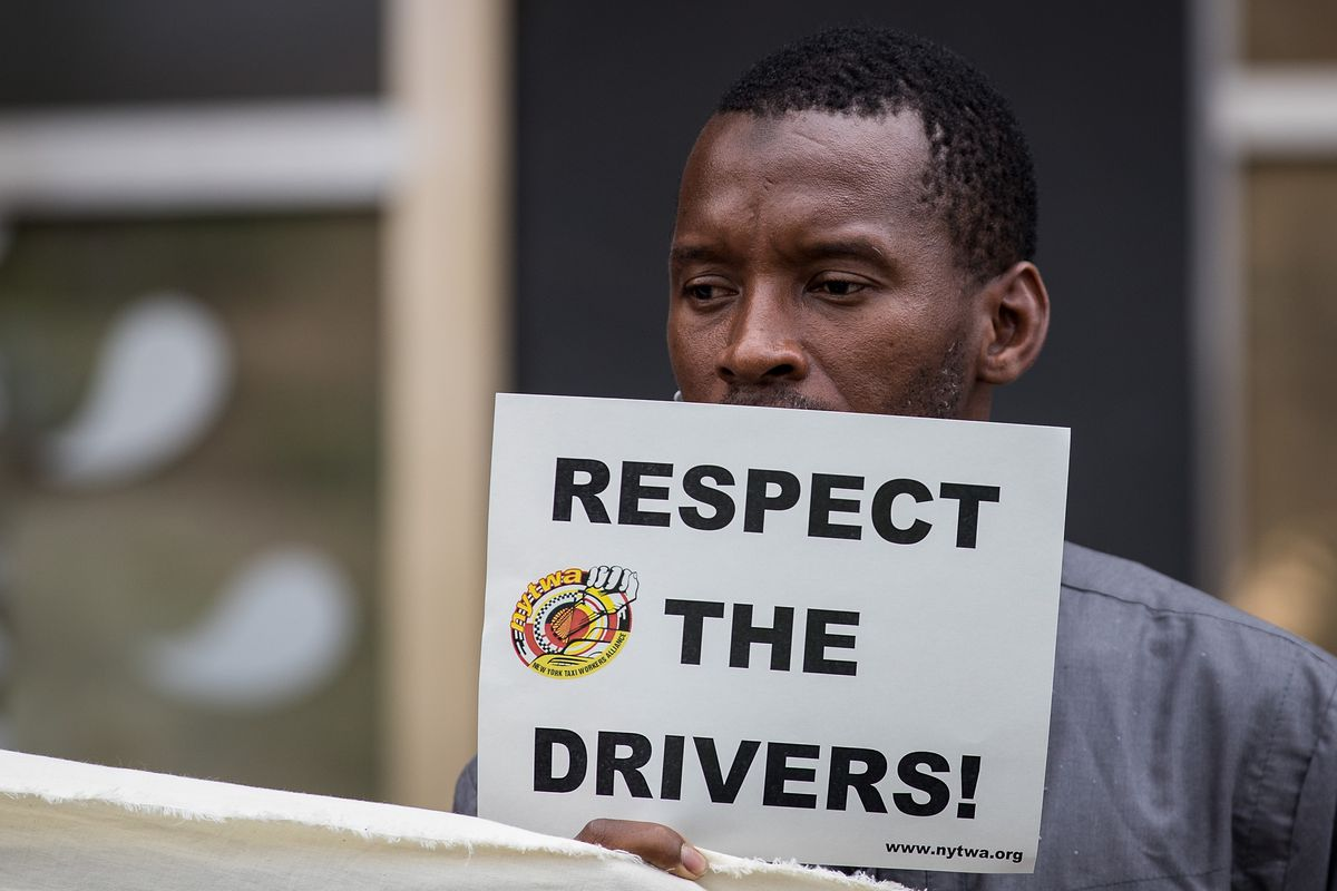 """A man is protesting by holding a sign that says """"Respect the drivers."""""""