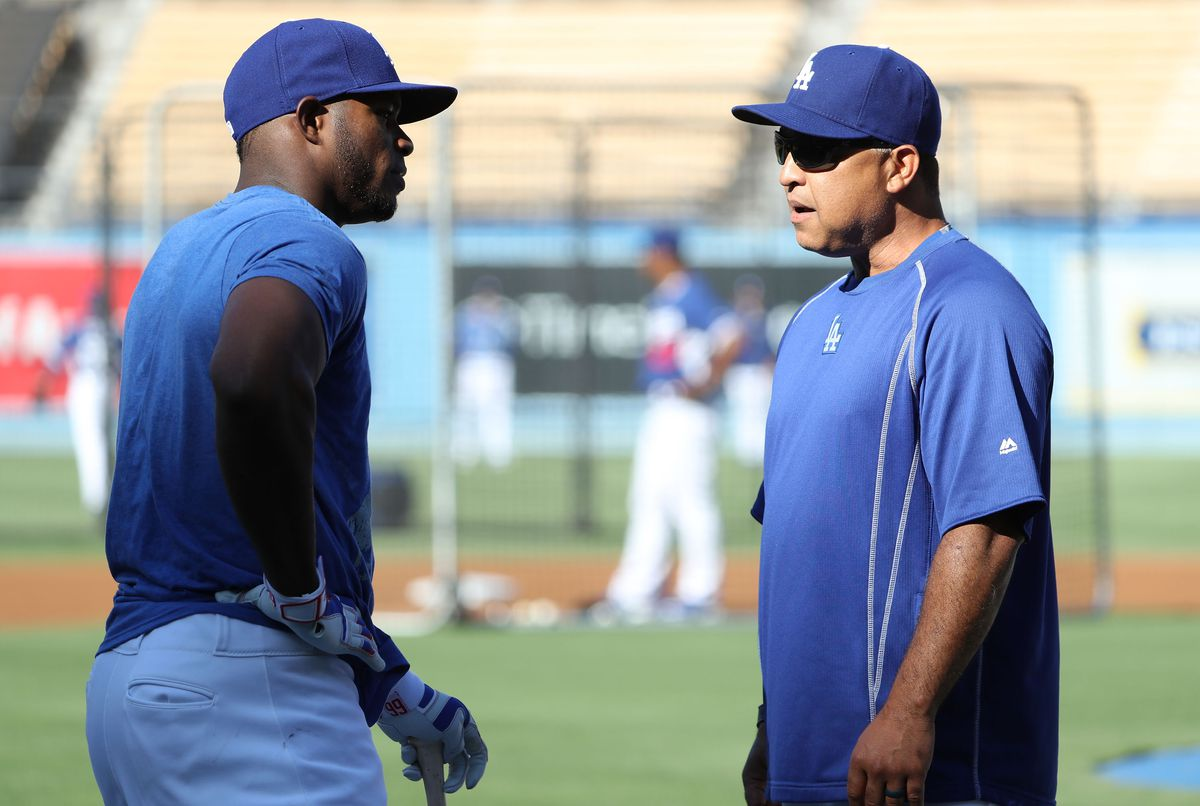 Los Angeles Dodgers manager Dave Roberts speaks with Yasiel Puig during practice