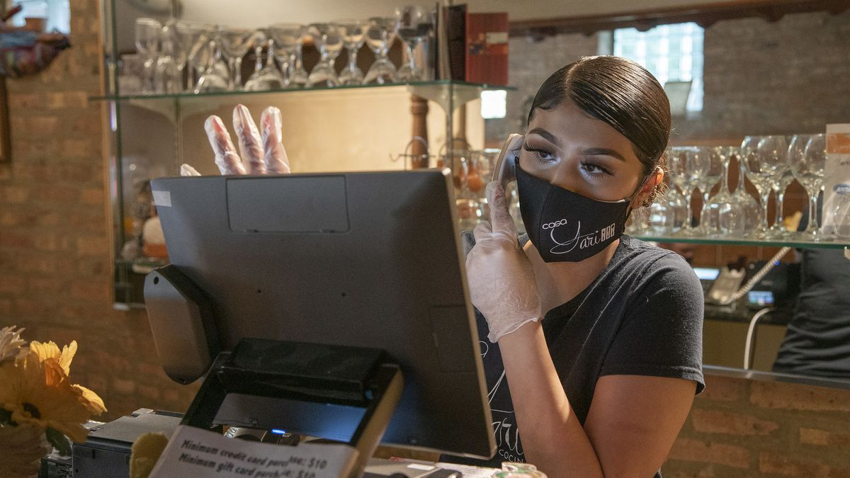 A masked worker takes phone orders.