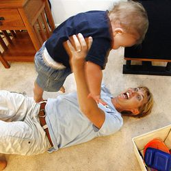 Faith Crabill plays with 11-month old son Caedan in their Salt Lake home Aug. 4. She buys disposable diapers for Caedan.