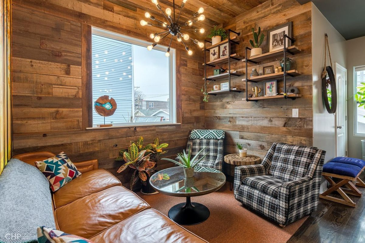 A sitting nook lined with rustic reclaimed wood has a leather couch and two plaid chairs.