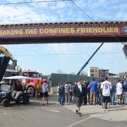 10:33 a.m. Debris hauler being loaded, as work cart passes, and fans wait for players -