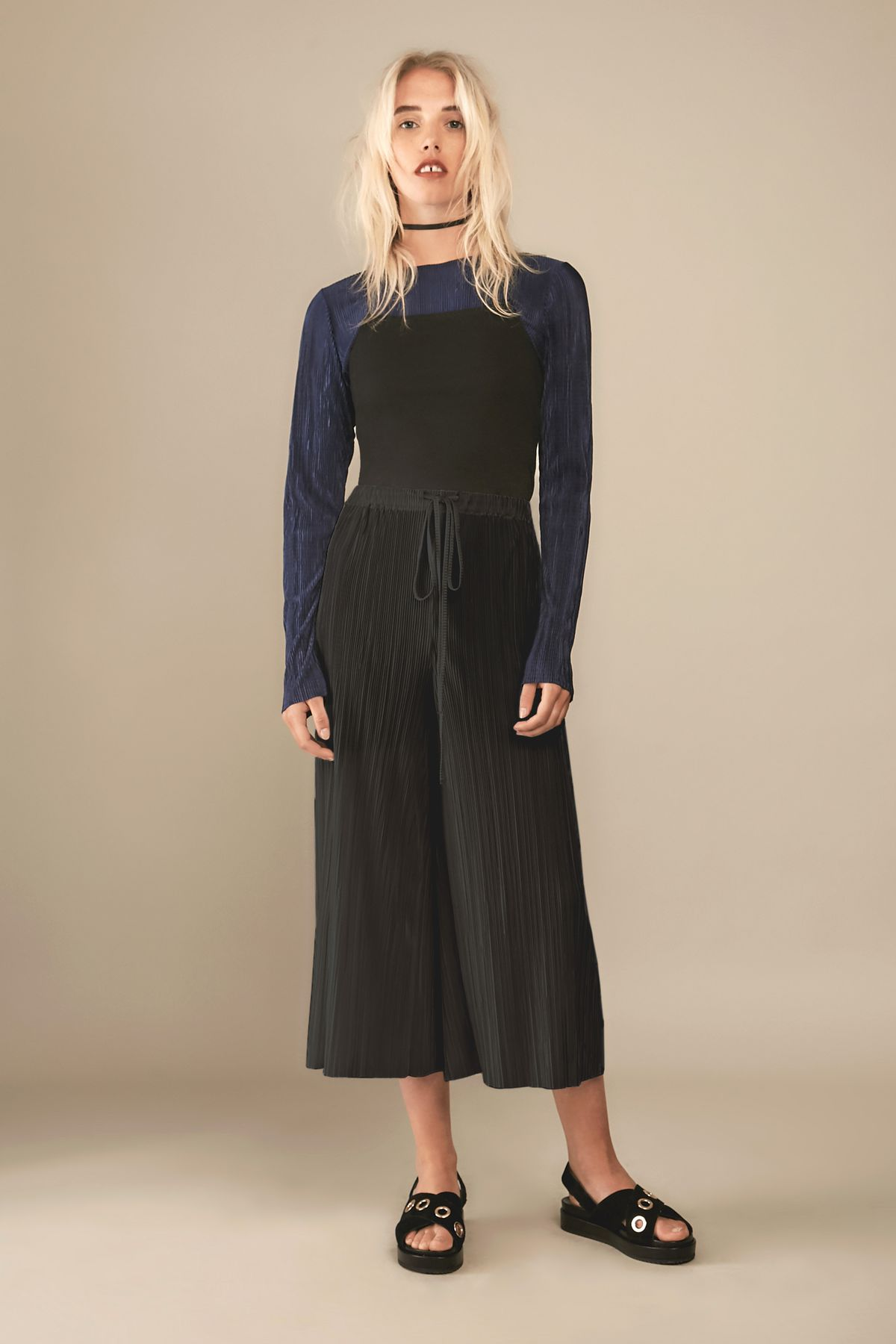 Blonde white model wearing black and navy outfit with black sandals
