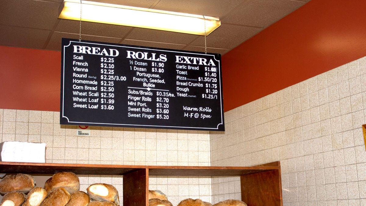 A black sign with white text listing prices for various breads and rolls. Backdropped by white subway tiles and red paint. A shelf with bread and rolls rests beneath the sign.