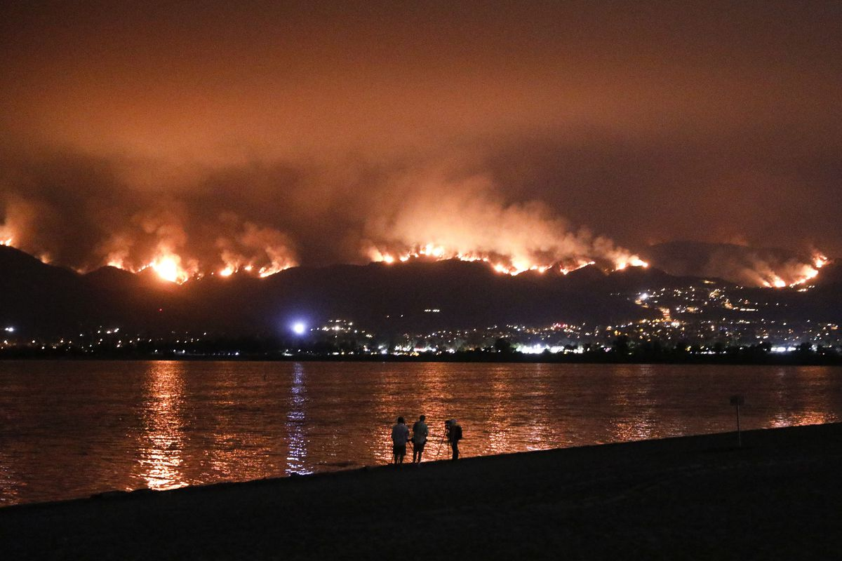 Onlookers are silhouetted against the reflection of a wildfire burning in the Cleveland National Forest in Lake Elsinore, Calif., Wednesday, Aug. 8, 2018. Evacuations have been ordered for several small mountain communities near where a forest fire contin