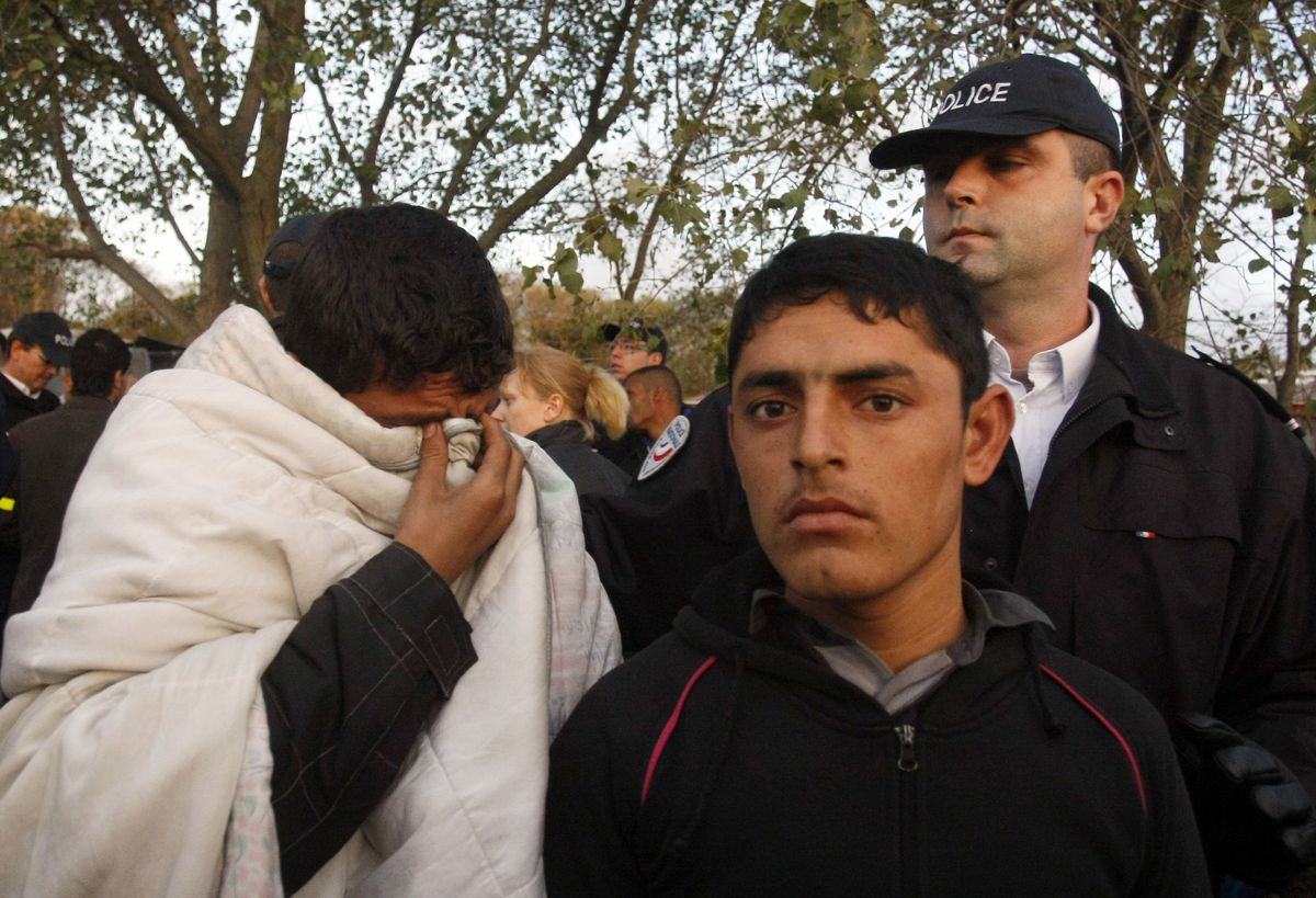 """In this Sept. 22, 2009 file photo, a police officer, top right, watches migrants in the camp known as the """"Jungle"""" in Calais, northern France. President Donald Trump's recent lament this week that immigration is """"changing the culture"""" of Europe is echoing"""