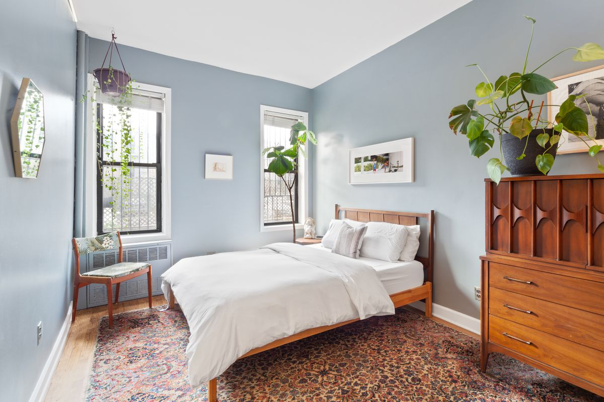 A bedroom with a medium-sized bed, several planters, two windows, a rug, and light blue walls.