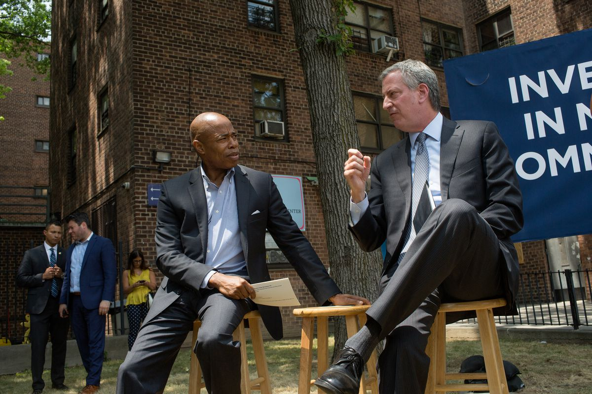Eric Adams and Bill de Blasio speak together while sitting on wooden stools in front of a large brick building.