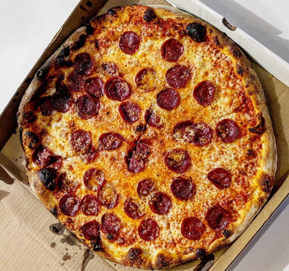 Overhead view of a New York-style pepperoni pizza in a takeout box