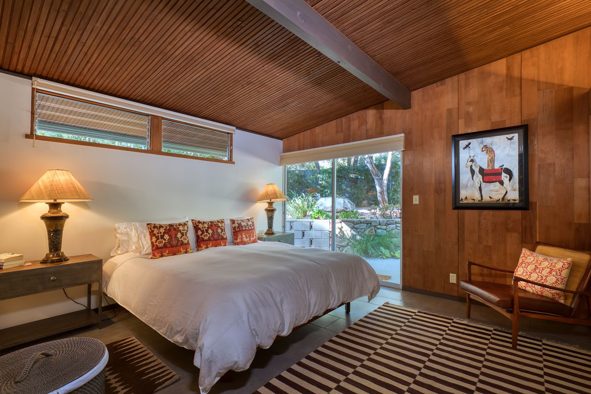A white king-size bed sits in a wood-paneled bedroom with a striped black and white rug.