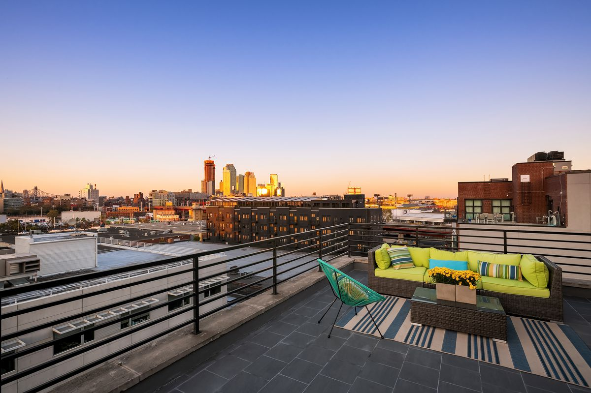 A rooftop with a bright green couch, a chair, and a coffee table.