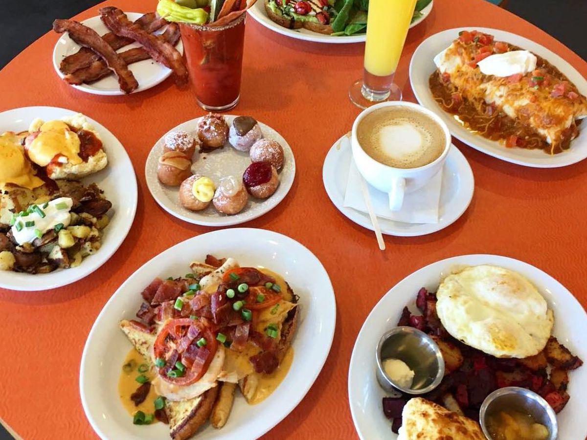 A close-up photo of a table covered with dishes containing assorted food from Jelly, including hashes, biscuits and gravy and salad, plus coffee, mimosas and bloody Marys in cups
