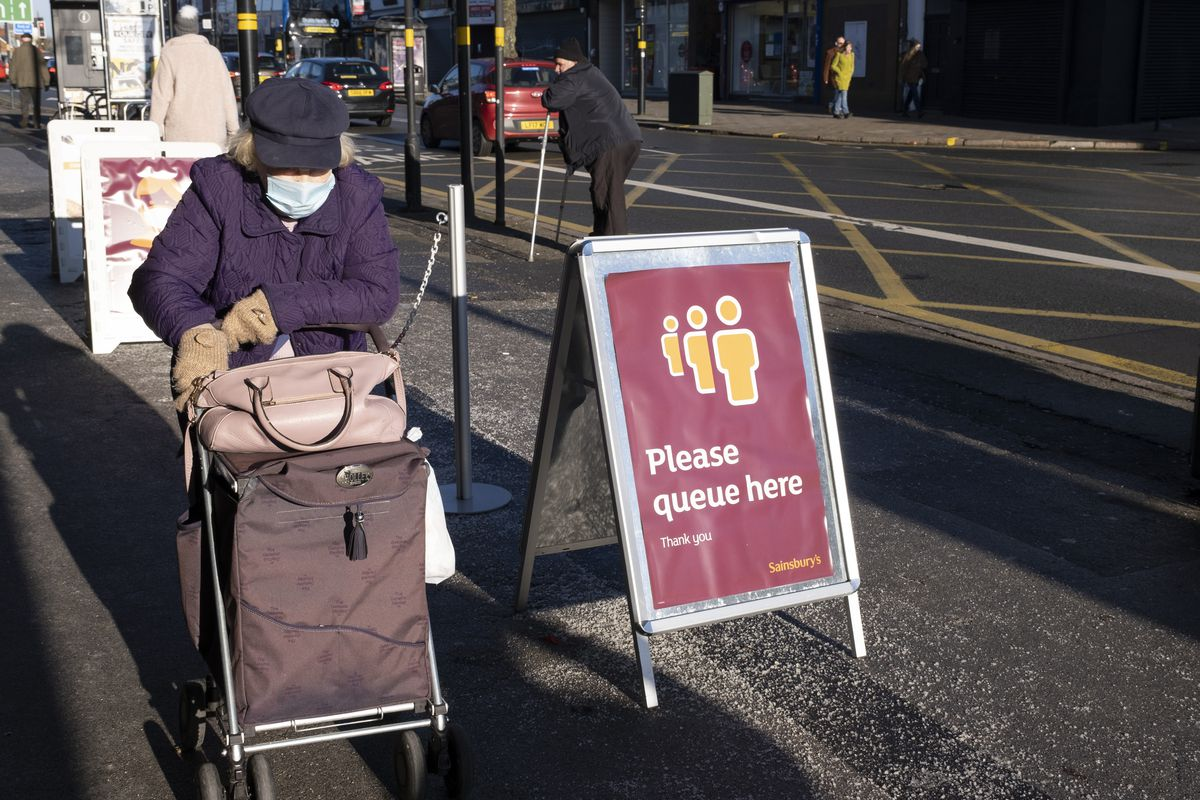 """Sainsburys supermarket signage saying """"please queue here"""" with a customer wearing a mask next to it"""
