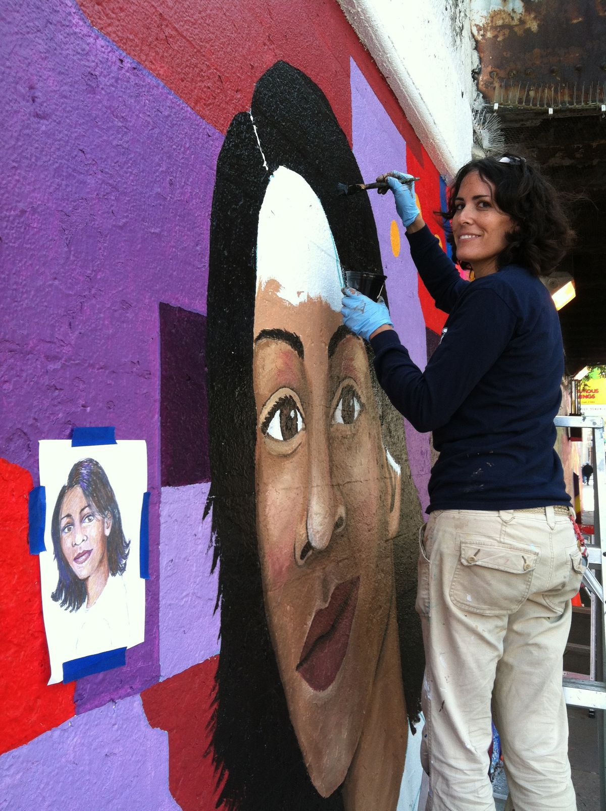 Lea Pinsky working on a mural on the city's North Side.