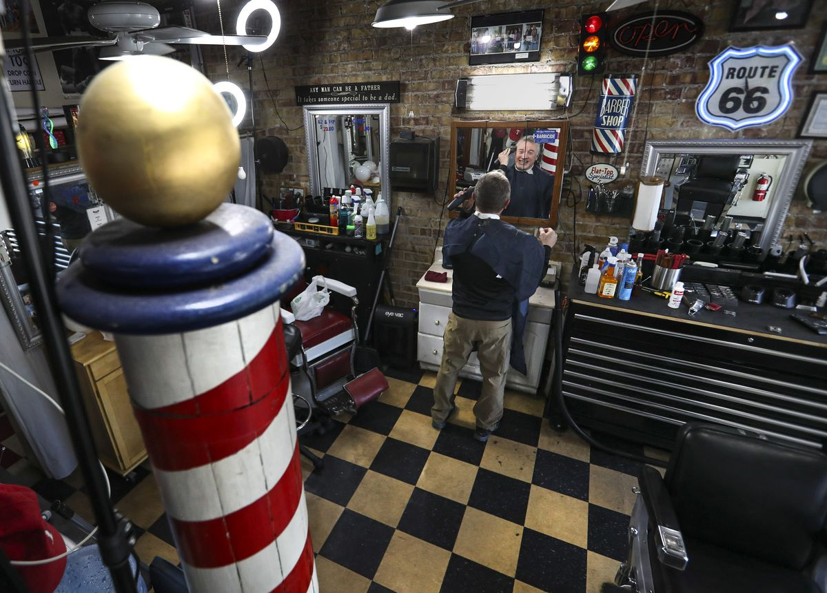 Perry's Barber Shop owner Perry Knuth cuts his own hair in his empty shop in downtown Salt Lake City on Wednesday, April 29, 2020. After being closed for several weeks, Knuth was in his shop for a trim and to clean before possibly reopening as COVID-19 restrictions are ease on May 1.